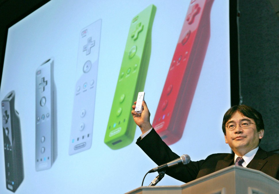 "Nintendo Co. Ltd. President Satoru Iwata displays a new smaller remote control device as he makes a  key cameo appearance at the annual Tokyo Game Show in Makuhari, east of Tokyo, Friday, Sept. 16, 2005. Wowing the audience with the new device, as simple as a TV remote switch,  for Nintendo's  Revolution machine, Iwata said  ""We thought about how everyone in the family uses the TV remote, but some people don't want to even touch the game controller.""   (AP Photo/Koji Sasahara)"